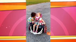 Watch a little girl help her friend learn to use her motorized wheelchair