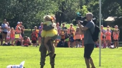 Watch a military mother surprise daughter at camp dressed as giant flower