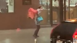 Woman with faulty umbrella is all of us in a bad rainstorm