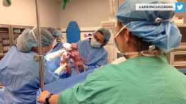 Twins who were photographed holding hands at birth are still incredibly close