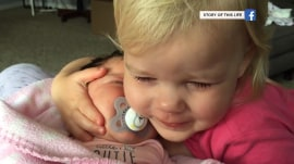 Watch this grumpy little girl get happy hugging her baby sister