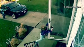 Watch this little girl hang onto door flung open by wind: What a grip!