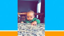 Baby sprayed with water doesn't appreciate dad's joke