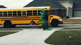 Watch this dad wait for his daughter's bus in a T. rex costume