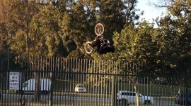 This BMX biker tries to flip over a fence (and doesn't quite make it)