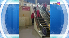 Watch Swiss skier ride the escalator – hanging by one arm!