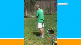 Dog hilariously gets in the way while man tries to water his lawn