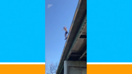 Watch this daredevil jump off a bridge – and come up with a fish