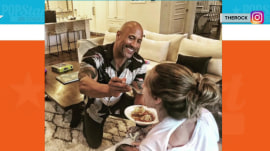 Dwayne Johnson feeds his girlfriend as she breastfeeds their baby