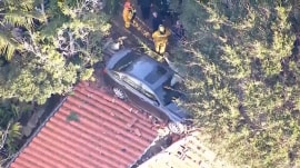 Car crashes, lands on top of a Southern California home