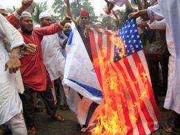 Image: Bangladeshi Muslims burn a U.S. flag and an Israeli flag as they shout slogans during a protest in front of National Press Club in Dhaka