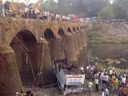 Image: Rescuers and bystanders look at the wreckage of a passenger bus after it fell from a bridge in Ratnagiri district