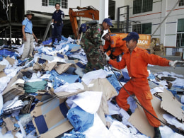 Image: Rescue workers and soldiers search through a site of the accident in a shoe factory in the Kong Pisei district of Kampong Speu province