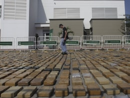Image: A police officer counts confiscated cocaine packages in the Caribbean port of Cartagena