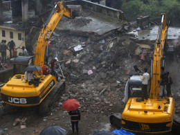 Image: Rescue workers use excavators to scour the debris for survivors at the site of a collapsed residential building on outskirts of Mumbai
