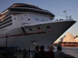 "Image: Onlookers stand below a Carnival Cruise Lines ship called the ""Carnival Spirit"" as it sits docked opposite the Sydney Opera House"