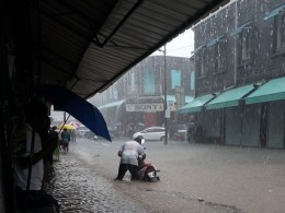 Image: A man pushes his motorcycle in flood waters during heavy torrential rain in Port Louis