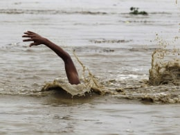 Image: A man swims in the flooded waters of river Yamuna to retrieve floating watermelons in New Delhi