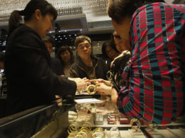 Image: Sales attendant shows gold bracelet to customers leaning over a half-empty display case at a jewellery store in Hong Kong
