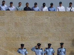 Image: Israeli police officers stand still as a two-minute siren is sounded before a ceremony at Yad Vashem in Jerusalem