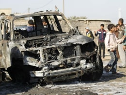Image: Residents gather at the site of a car bomb attack in the Shuala district in Baghdad