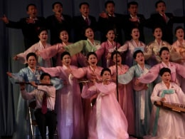 Image: Performers sing a song about North Korea's late leader Kim Jong Il at the opening of the April Spring People