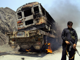 Image: Tribal policeman stands guard near a burning NATO supply convoy in Jamrud, Khyber tribal region of Pakistan