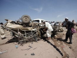Image: Security officials collect evidence from a damaged vehicle at the site of a bomb attack after a bomb blast in Jalozai camp iin Nowshera