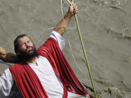 Image: An actor portraying Jesus Christ is submerged in the water during a baptism ceremony as part of Catholic Holy Week celebrations at the Rimac river in Lima