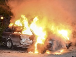 Image: A car set on fire burns following riots in the Stockholm suburb of Kista