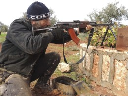 Image: A member of the fighting vanguard besieging Taftanaz air base near Idlib, aims his weapon