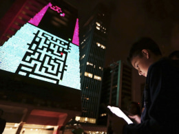 "Image: A boy uses an iPad to play a game, which is projected onto the Fiesp building, during the ""Play!"" exhibition in Avenida Paulista"