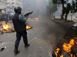 Image: A police officer shoots rubber bullets during a clash with activists of Hefajat-e Islam in Dhaka