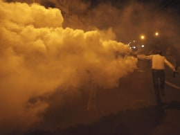 Image: A protester, who opposes Egyptian President Mohamed Mursi, throws a tear gas canister, which was thrown earlier by the riot police, during clashes in front of the presidential palace in Cairo