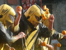 Image: A member of a rival team is hit by oranges during an annual carnival battle in the northern Italian town of Ivrea
