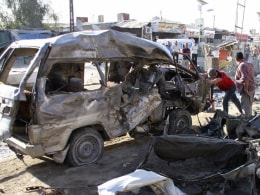 Image: Residents gather at the site of a car bomb attack in Baghdad