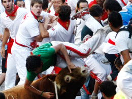 Image: A bull gores a runner during the the San Fermin festival in Pamplona