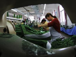 Image: In this Monday, May 20, 2013 photo, workers sew fabrics at a garment factory in Jiujiang in central China.
