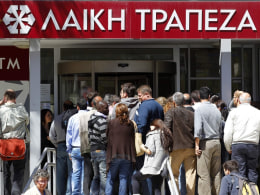 Image: People wait to enter at a branch of Laiki Bank shortly after it opened on Thursday in Nicosia, Cyprus.