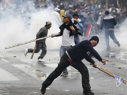 Image: A construction worker throws a stone at riot police officers during a demonstration against the government, in Lima
