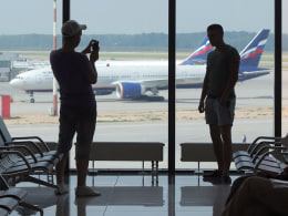 Image: A passenger takes a photo with a mobile phone  in the transit zone at Sheremetyevo airport in Moscow.