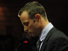 Image: Oscar Pistorius stands at the dock before the start of proceedings at a Pretoria magistrates court
