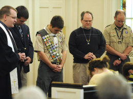 Image: Eagle Scouts bow their heads in prayer during services