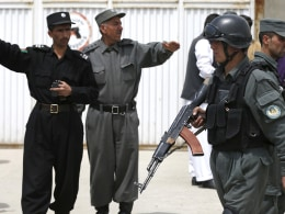 Image: Afghan policemen stand outside Cure Hospital after three foreigners were killed in Kabul