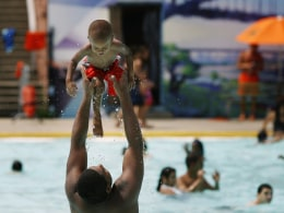 Image: A man tosses a small child in the air while standing in the water at the Astoria Park Pool in New York