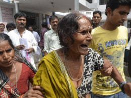 Image: A woman cries after her grandson, who consumed spurious meals at a school on Tuesday, died at a hospital in Patna