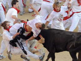A heifer attacks a reveller in the Plaza de Toros at the end of the second running of the bulls of the San Fermin festival in Pamplona.