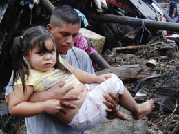 Image: A man carries a girl on a street damaged by heavy rains in Verapaz