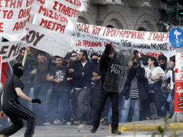 Image: A protester holds a police shield during demonstration in Athens