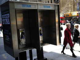 People walk by empty public pay phone bo